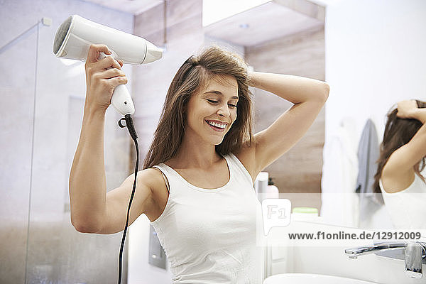 Portrait of laughing woman using hair dryer in the bathroom