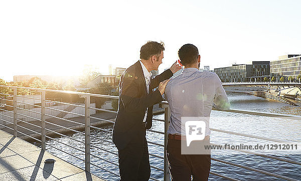 Two businessmen discussing on a bridge in the city