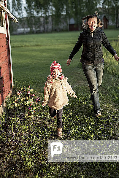 Finland  Kuopio  mother with daughter running at a cottage in the countryside