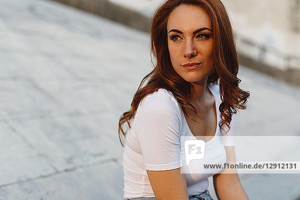 Portrait of redheaded young woman using cell phone outdoorsat sunset