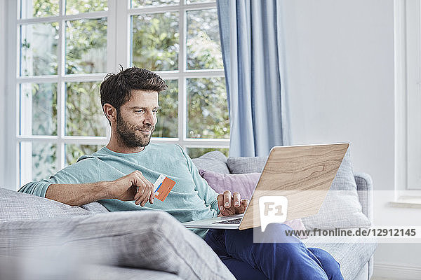 Smiling man at home shopping online
