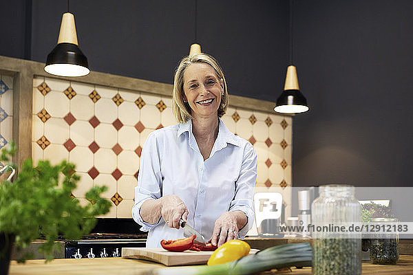 Portrait of smiling mature woman chopping bell pepper in kitchen
