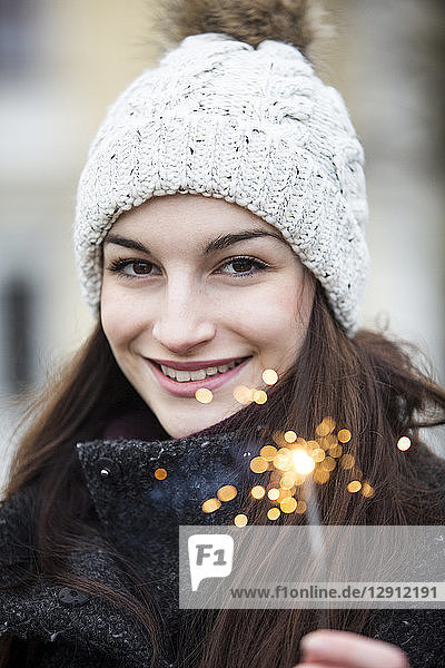 Portrait of smiling young woman with sparkler wearing bobble hat
