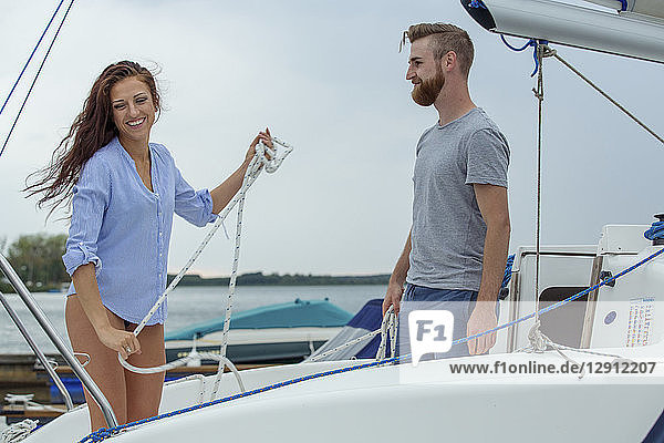 Couple unmooring sailing boat