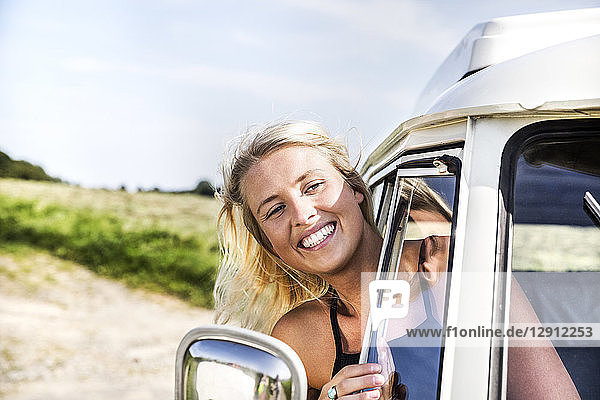 Happy woman looking out of window of a van