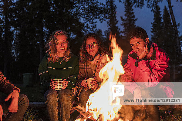 Group of friends sitting at a campfire  talking and drinking tea