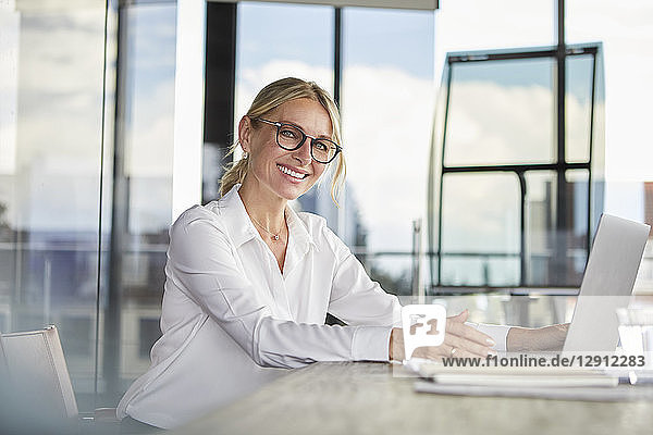 Businesswoman sitting at desk  using laptop  smiling friendly