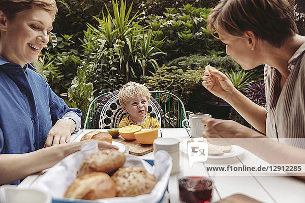 Two happy mothers at breakfast table outdoors with their child