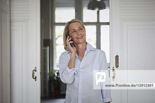 Smiling mature woman on cell phone at home