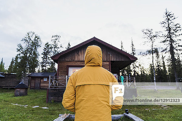 Man standing in front of log cabin  rear view