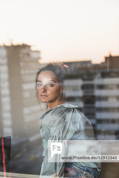 Portrait of young woman behind windowpane with reflection of the city