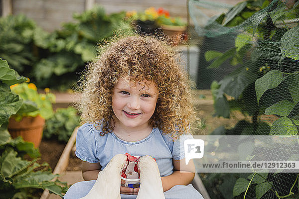 Portrait of happy little girl feeding chickens in allotment