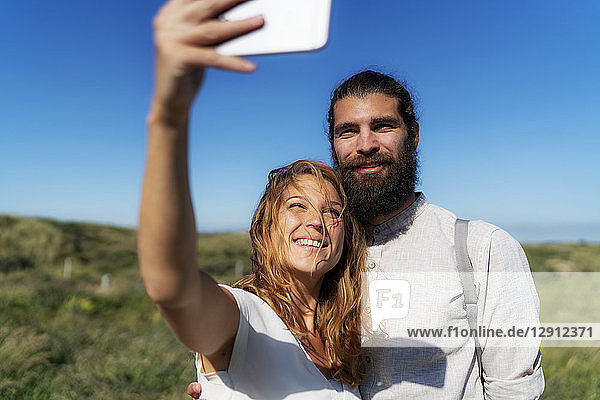 Young couple taking smartphone selfies on the beach