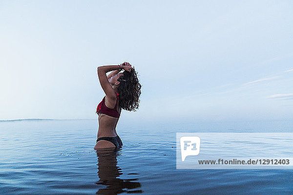Woman wearing bikini  standing in water of a lake