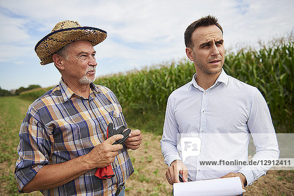 Farmer and businessman discussing on the field