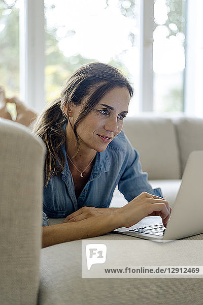 Smiling mature woman lying on couch at home using laptop
