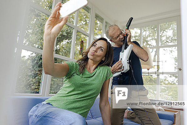 Mature woman taking a selfie at home with man playing toy electric guitar