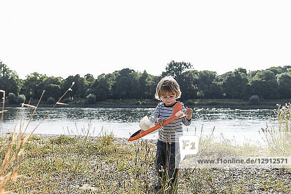 Boy playing with a toy plane at the riverside