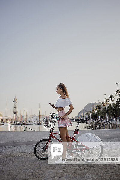 Fashionable young woman exploring Barcelona with a bicycle  using smartphone