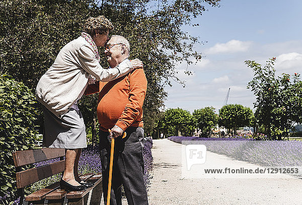 Senior couple having fun in the park  woman standing on bench kissing senior man on forehead