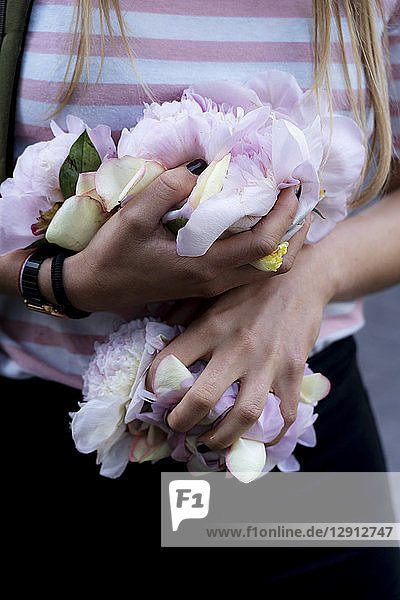 Hands of young woman  holding peonies
