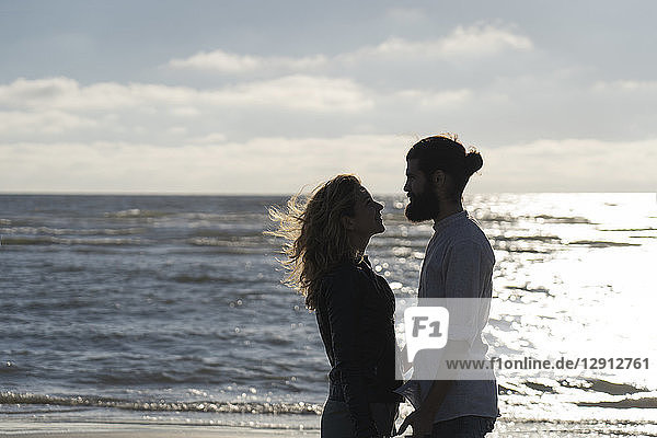 Young couple looking at each other  standing at the sea