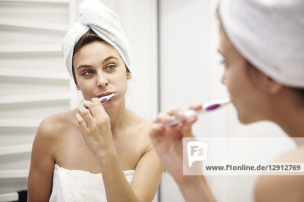 Mirror image of young woman in bathroom brushing her teeth