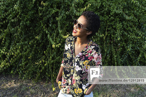 Smiling young woman wearing sunglasses and colourful blouse