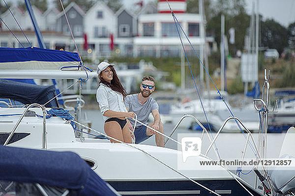 Couple unmooring sailing boat