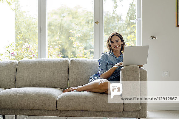 Smiling mature woman sitting on couch at home with laptop