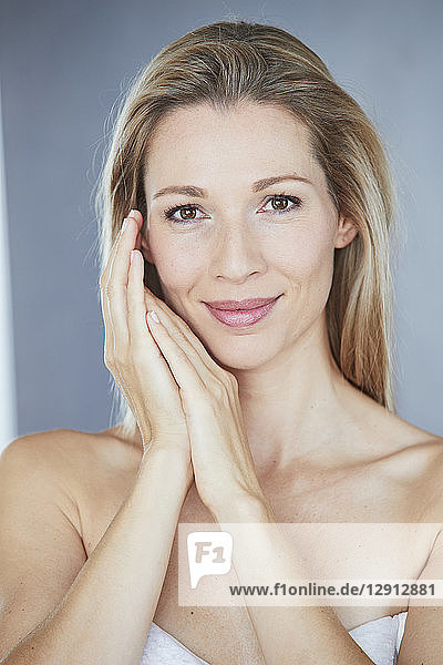 Portrait of smiling blond woman wrapped in towel