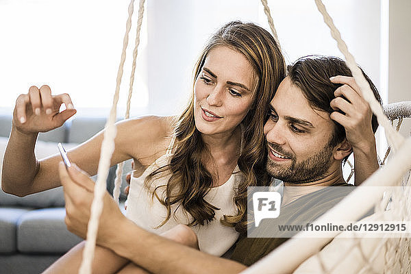 Couple in hanging chair at home looking at tablet