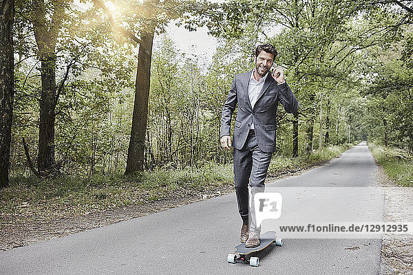 Businessman riding skateboard and talking on smartphone on rural road