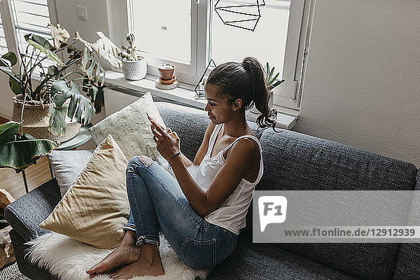 Young woman sitting on the couch at home using mobile phone