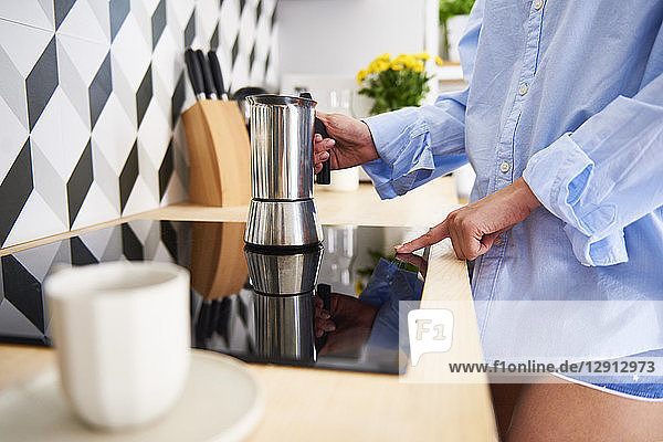 Young woman preparing coffee in the morning