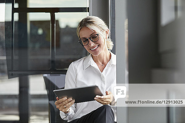 Serene businesswoman sitting on ground in office  using digital tablet