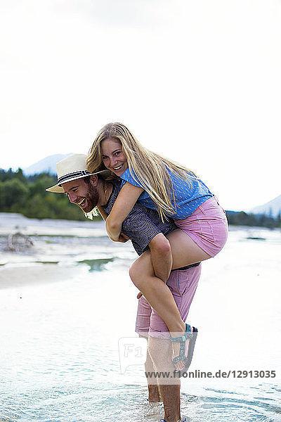 Young man giving girlfriend piggyback ride  river