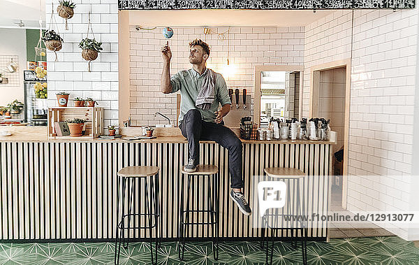 Young man working in his start-up cafe  spinning a little globe on his forefinger