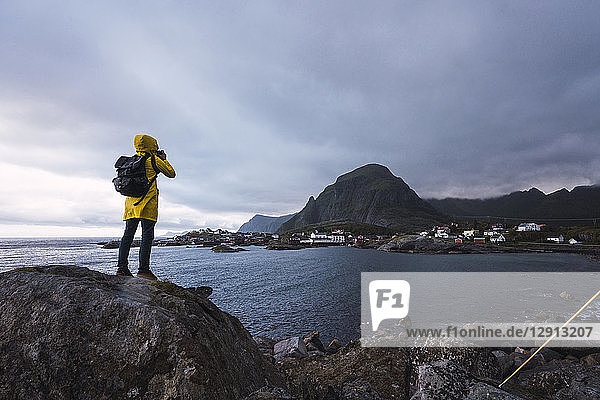 Norway  Lofoten  rear view of man standing on a rock at the coast taking a picture