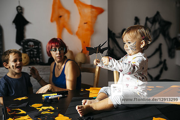 Baby girl playing with halloween decoration at home while mother and brother watching her