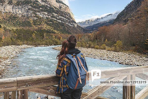 Spain  Ordesa y Monte Perdido National Park  back view of woman with backpack on wood bridge