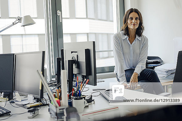 Mature businesswoman sitting o desk in office  smiling
