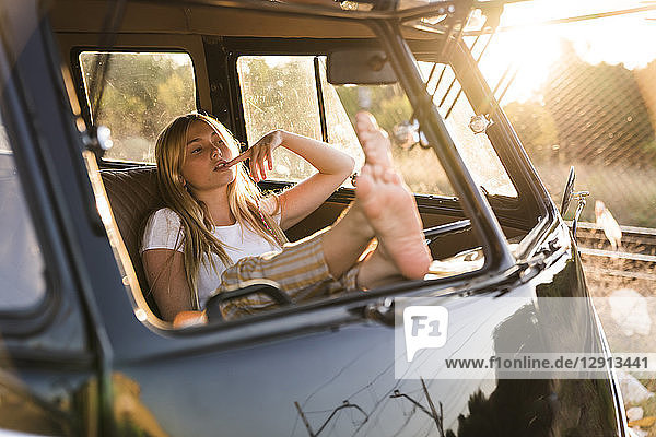 Young woman sitting in a van with feet up
