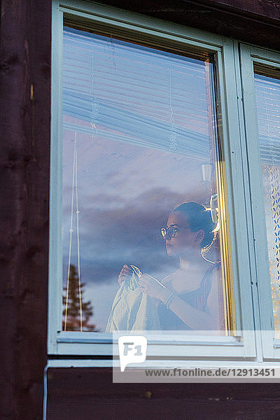Young woman standing at window  changing clothes