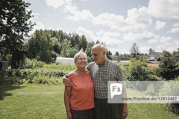 Happy senior couple standing in the garden