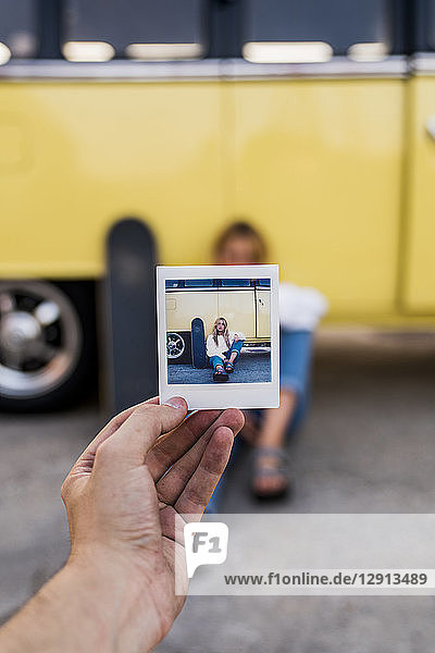 Hand holding instant photo of young woman with skateboard sitting at a van
