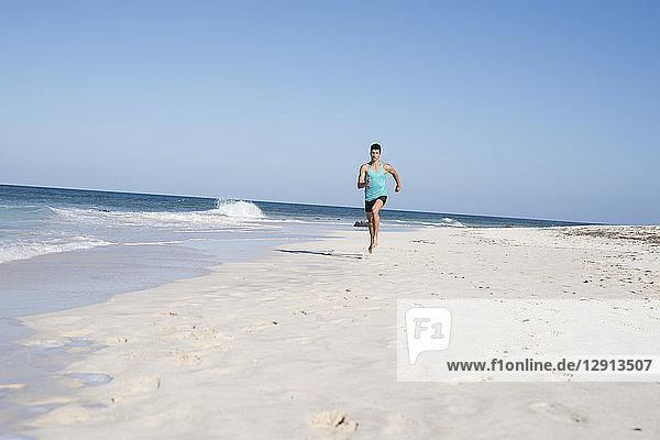 Spain  Canary Islands  Fuerteventura  young man running on the beach