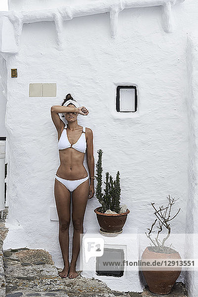 Young woman wearing white bikini leaning against white wall covering eyes with her arm
