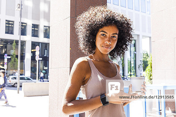 Portrait of smiling young woman with coffee to go and cell phone