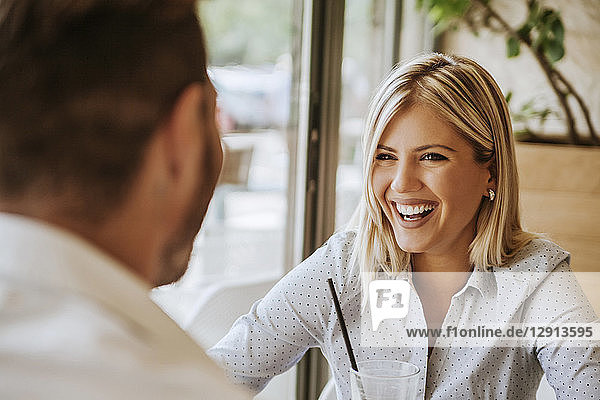 Happy young woman looking at man in a cafe